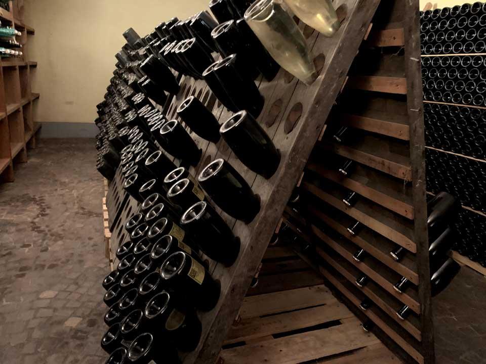 Bottiglie di spumante metodo classico disposte nel pupitres, il cavalletto inclinato ideato da Antione Muller